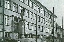 Socha Pallas Athény nad vchodem do chomutovského gymnázia na fotografii z roku 1933.