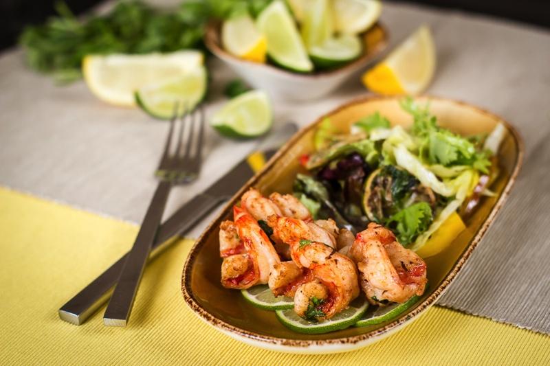 Marinované tygří krevety slimetkou a koriandrem na salátu ztrhaných listů a bylinkovou bagetou